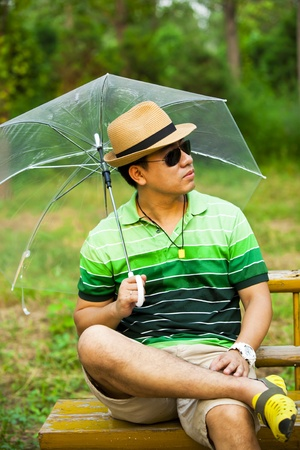 Asian young man holding an umbrella and sitting on park bench photo