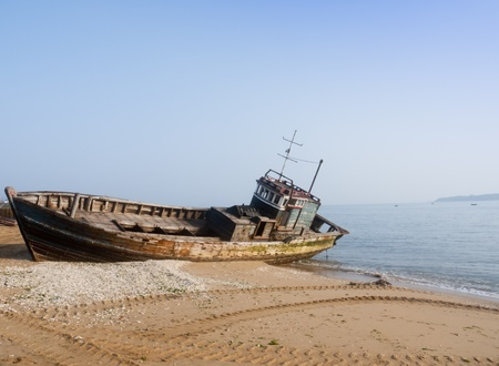 derelict: Rusty ship at the beach