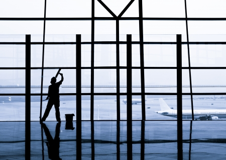 mujer limpiando: trabajador de limpieza de ventanas en el aeropuerto internacional de Beijing, China Editorial
