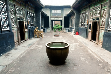 chinese traditional house: Traditional Chinese Building. A big vat placed in the yard for fireproofing, another meaning is collecting wealth. Water means wealth in traditonal culture. Pingyao County, Shanxi Province, China Editorial