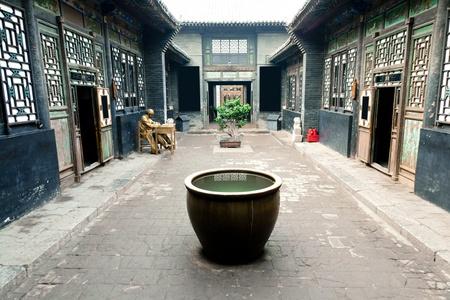 Traditionele Chinese Building. Een groot vat geplaatst in de tuin voor het brandwerend maken, wordt een andere betekenis verzamelen rijkdom. Water betekent rijkdom in traditionele cultuur. Pingyao County, de provincie Shanxi, China Redactioneel