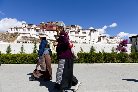 potala: Lhasa, Tibet, China - 08 October, 2011: Female buddhist pilgrims passing by the Potala Palace, Lhasa, Tibet, China.