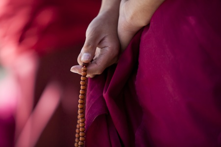 buddhism: Prayer beads in monk s hand