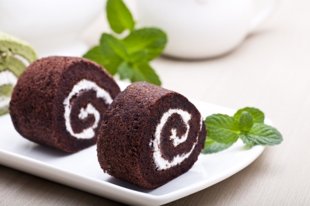 Chocolate swiss roll with green mint leaves