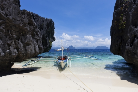 palawan: Lonely boat, dark cliff, blue sea and sky, white beach, El Nido, Palawan, Philippines