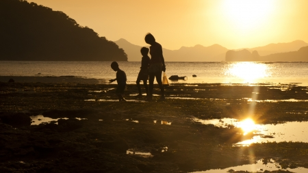 Mother and children silhouette at sea sunset, they are walking along the beach  photo