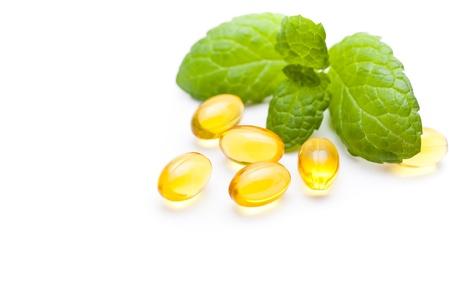 Gel vitamin capsules and green leaf 免版税图像 - 16491376