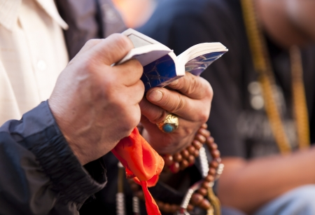 buddhism prayer belief: A Tibetan pilgrim is reading sutra and praying in front of the Jokhang Temple in Lhasa, Tibet