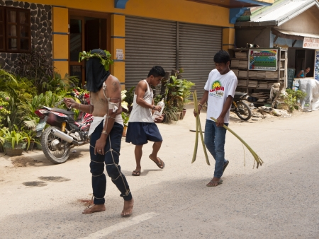 El Nido, Philippines - April, 06, 2012: A masked and binded papist is walking down the street with lash suffering by himself for expiating sin at Easter day. Two helpers are following him while preparing water and lash. A woman is watching them from her h Stock Photo - 17437254