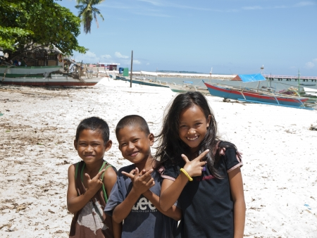 filipino ethnicity: El Nido, Palawan, Philippines - April 3, 2012: Two boy and a girl smiling and making cute gestures to camera at the beach.