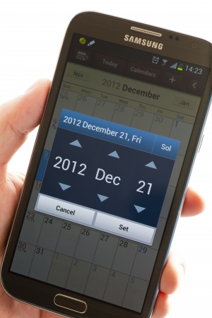 A hand holding an a Samsung smartphone Galaxy Note II displaying calendar date Dec, 21, 2012.