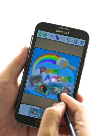 note pad and pen: A man holding a smart phone of Samsung Galaxy Note II and using pen touch the screen which displaying paper artist program.