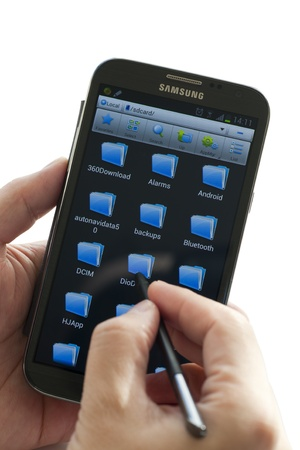 samsung galaxy: A man holding a smart phone of Samsung Galaxy Note II and using pen touch the screen which displaying folders.