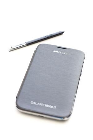 note pad and pen: Samsung Galaxy Note II smart phone on white background.