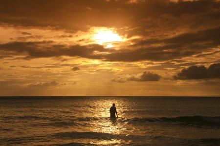 hombre solitario: Hombre solo en la silueta caminando en el mar al atardecer