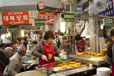 korean culture: Seoul, South Korea - April 27, 2013: A female vendor is cooking traditional Korean pie for customers at the Gwangjang Market which is the nation Editorial