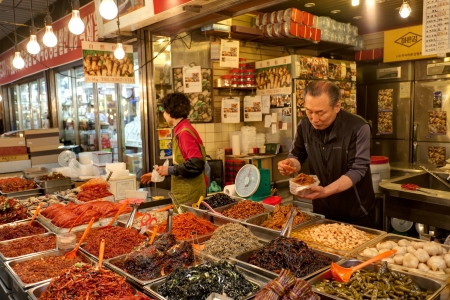 Seoul, South Korea - April 27, 2013: Vendors are selling kimchi at local market. Kimchi, the staple Korean food, is long-term fermented vegetables served as a side dish. the Gwangjang Market is the nation