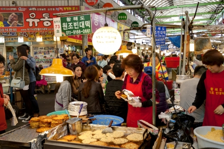 Seoul, South Korea - April 27, 2013: Customers are sitting around a small table and eating traditional Korean food. A female vendor is cooking Korean pie. The Gwangjang Market which is the nation's first market and also a popular tourist destination.