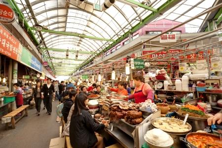 ソウル、韓国 - 2013 年 4 月 27 日: 女性ベンダーは国の最初の市場とも人気の観光地である広壮市場での顧客のための伝統的な韓国料理を調理します