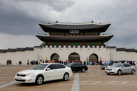 Seoul,South Korea - May 01,2013: Tourists visiting Gyeongbokung Palace and cars drving across the road before Gwanghwamun Gate. 新闻类图片