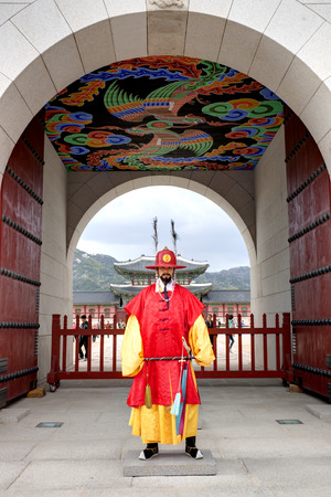 korean man: Seoul, Republic of Korea - May 01, 2013: A royal guards in red uniforms standing in front of the main gate to Gyeongbokgung Palace.