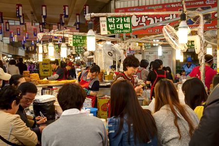 Seoul, South Korea - April 27, 2013 Female vendors are cooking traditional Korean food for customers at the Gwangjang Market which is the nations first market and also a popular tourist destination