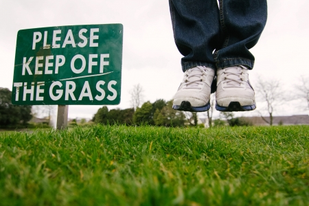 keep out: keep of the grass sign with levitated feet