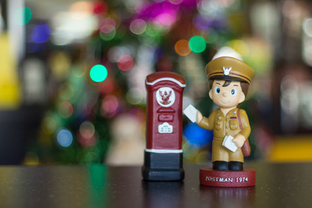 Soft focus doll postman standing letterbox. Stock Photo