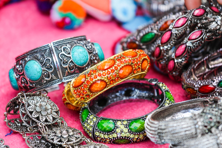 artifacts: Focus your silver bracelet with jewelry and colorful background of many artifacts from Thailand.