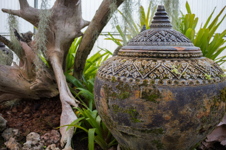 Ancient clay pot to collect water in landscaped gardens.