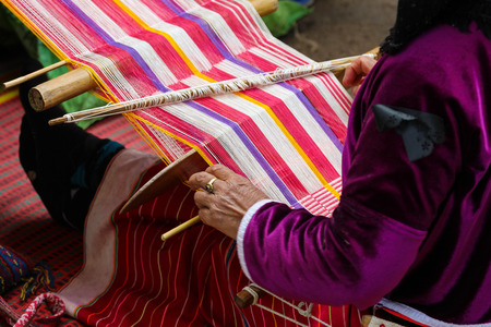 Native woman weaving intricate llama garments using a traditional hand loom. Stock Photo