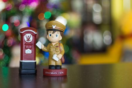 Soft focus doll postman standing letterbox. Фото со стока