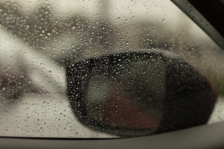 Raindrops on the car rearview mirror. Heavy rain outside