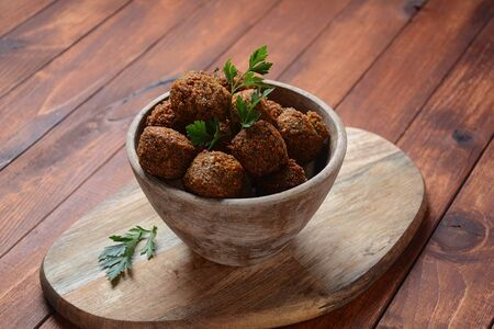 Falafel balls with parsley in wooden bowl with tahini sauce. Vegan healthy food Reklamní fotografie