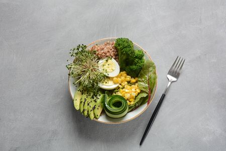 Green vegetarian buddha bowl lunch with boiled egg, avocado, corn, arugula beet leaves,fresh cucumber, buckwheat, broccoli sprouts.Healthy vegan food concept
