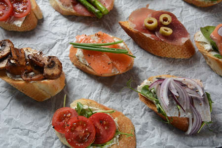 Brushetta or traditional Spanish tapas. Appetizers with Italian antipasti snacks. Variety of small sandwiches with prosciutto, cherry tomatoes, salmon, cream cheese, cucumber, radish, asparagus Banque d'images