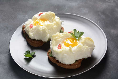 Delicate baked egg. Orsini eggs in the cloud. French breakfast.Cloud egg on toast