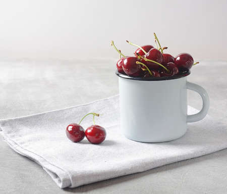Fresh red cherries in a cup on a table napkin Фото со стока