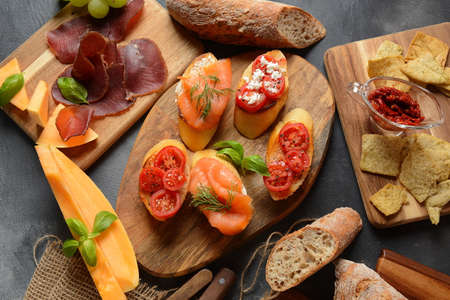 Brushetta or traditional Spanish tapas. Appetizers with Italian antipasti snacks. Variety of small sandwiches with cherry tomatoes, salmon, cream cheese. Prosciutto served with melon and basil Banque d'images