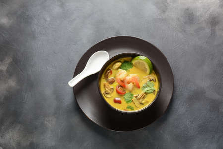 Tom Yam kung Spicy Thai soup with shrimp, seafood,tomatoes, mushrooms, lemongrass, coconut milk, ginger and chili pepper in bowl . Traditional Thai food Reklamní fotografie