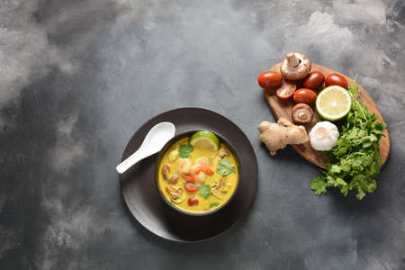 Tom Yam kung Spicy Thai soup with shrimp, seafood,tomatoes, mushrooms, lemongrass, coconut milk, ginger and chili pepper in bowl . Traditional Thai food Фото со стока