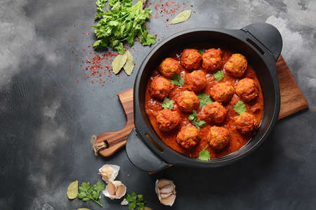 Meatballs in sweet and sour tomato sauce with spices served in a frying pan on dark background . Top view