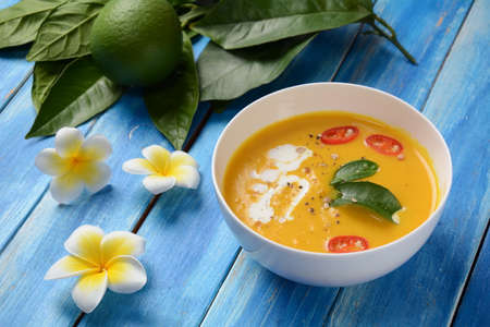 Thai spicy pumpkin and coconut milk soup with kaffir lime leaves , red chilli and galangal roots powder.