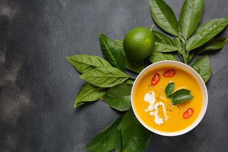 Thai spicy pumpkin and coconut milk soup with kaffir lime leaves , red chilli and galangal roots powder. Vegan, healthy food, gluten-free. Paleo- diet