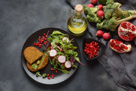 Broccoli schnitzel served with pomegranate salad. Healthy vegan food .
