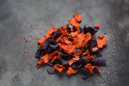 Baked vegetable chips- garnet sweet potato, purple sweet potato,carrot and beetroot. Gluten-free, dairy-free and vegan. Healthy food concept