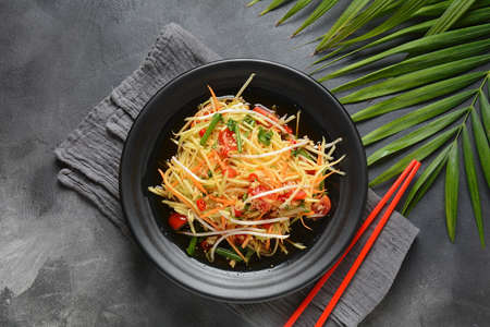 Delicious Som Tam -Thai green papaya salad) with green beans, tomatoes, peanuts. Thai street food . Healthy vegan food Zdjęcie Seryjne