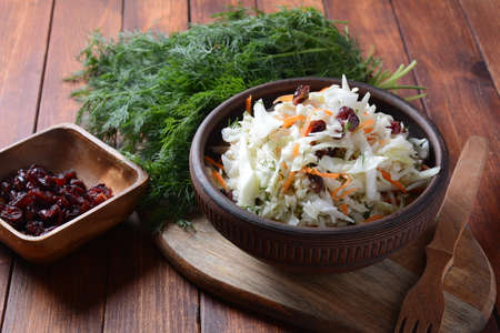 Cabbage salad with carrot, smoked almonds and dried cranberries. Coleslaw Salad. Fermented cabbage- Russian cuisine. Healthy vegan food concept.