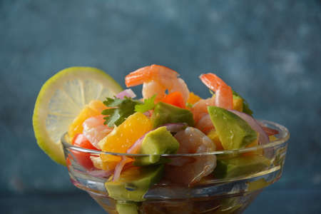 Ceviche salad with shrimps, oranges and avocado in glass bowl on a dark or grey background. Latin American food. Delicious, freshly made shrimp ceviche. Shrimp marinated in lime and orange . Zdjęcie Seryjne