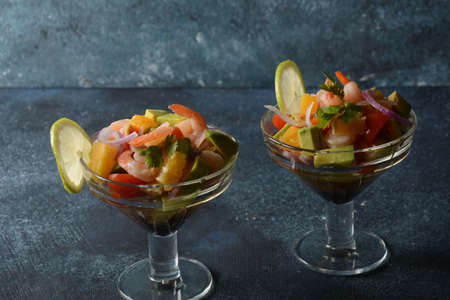 Ceviche salad with shrimps, oranges and avocado in glass bowl on a dark or grey background. Latin American food. Delicious, freshly made shrimp ceviche. Shrimp marinated in lime and orange .
